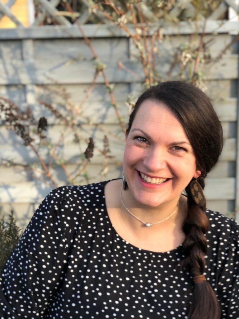 Porträtfoto im Garten von Lea Schulz (schaut lächelnd mit leicht schrägem Kopf in die Kamera)